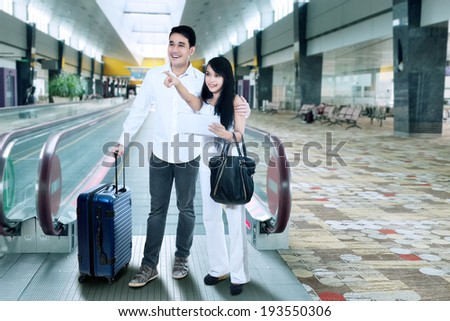 Young couple with suitcase standing at airport - stock photo