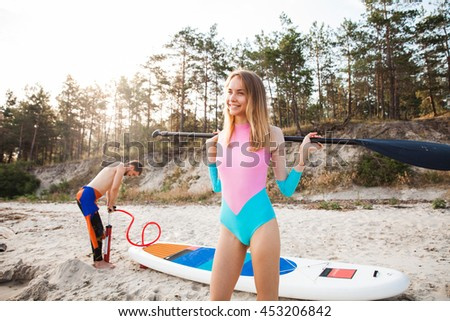 Young couple with sup board on the beach. Focus on woman, man pumping up the board. Concept of harmony with the nature, free and healthy living, freelance, remote business. - stock photo