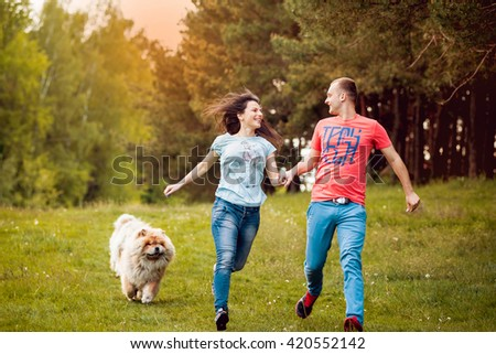 Young couple with the dogs in the park. - stock photo