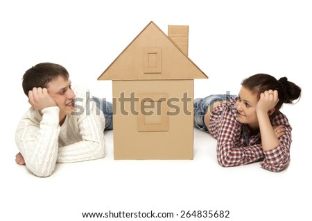 Young couple with the house of cardboard, isolated on white background - stock photo