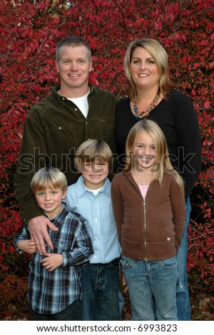 Young couple with three children in front of a burning bush - stock photo