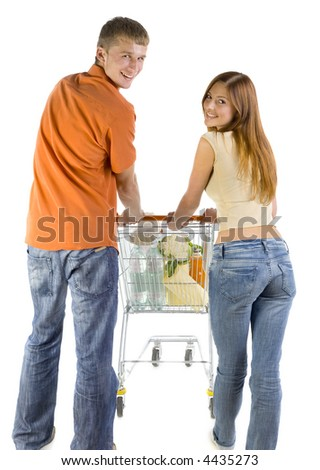 Young couple with trolley. Smiling and looking behind at camera. White background - stock photo