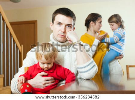 Young couple with two children having quarrel in living room at home - stock photo