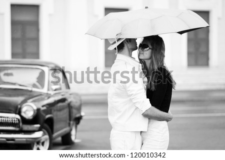 Young couple with umbrella in love - stock photo