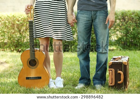 Young couple with vintage suitcase and guitar outdoors - stock photo