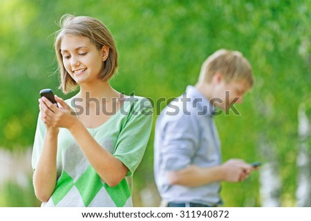young couple woman and man talking on phone - stock photo