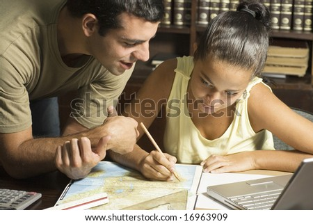 Young couple working at desk with a protractor, laptop computer, and a map. - stock photo