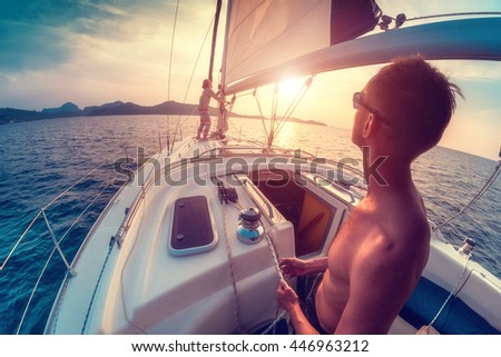 Young couple working with sail and ropes on the sailing boat