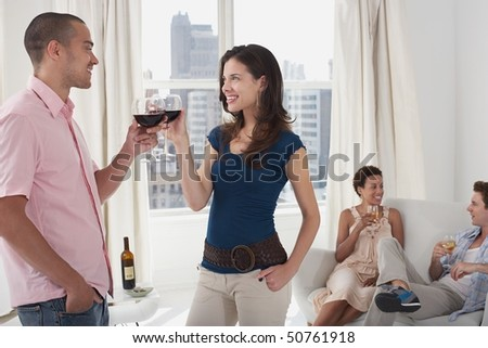 Young couples drinking wine in living room - stock photo