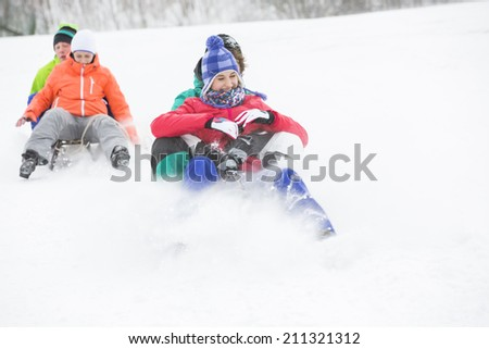Young couples enjoying sled ride on snow covered slope