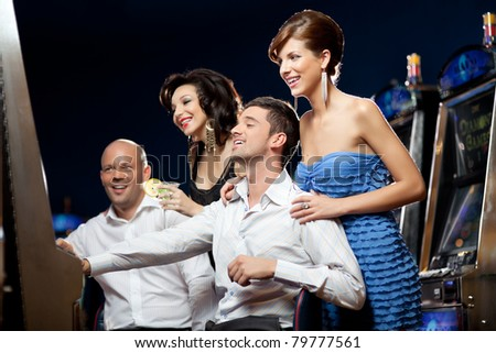 young couples playing at slot machine - stock photo