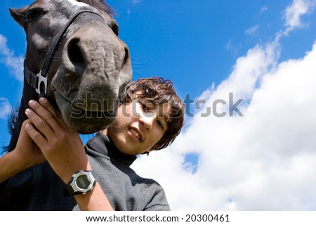 Young cowboy and his favorite horse Jezgeeck, Kazakhstan - stock photo