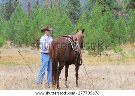 Young cowboy working with his horse in the field - stock photo