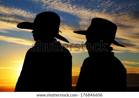 young cowboys silhouette wearing hats sunset background - stock photo