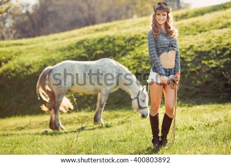 Young Cowgirl and Horse Outdoors. Wild West Retro Style Shoot - stock photo