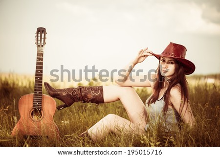 young cowgirl in red hat at spring meadow with guitar - stock photo