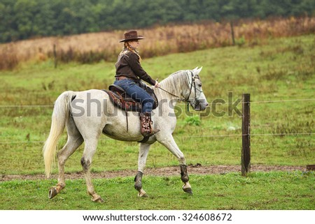 young cowgirl on white horse  - stock photo