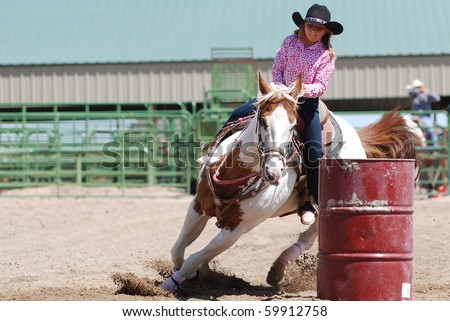 Young cowgirl riding a beautiful paint horse in a barrel racing event at a rodeo. - stock photo