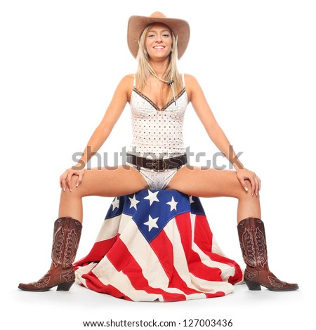 Young cowgirl sitting on a american flag. Retro style picture. - stock photo