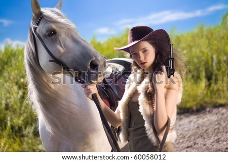 young cowgirl with gun outdoor - stock photo