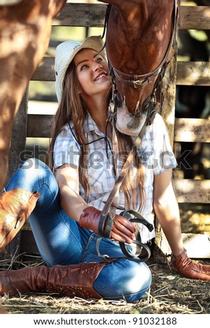 Young cowgirl with horse kissing her - stock photo