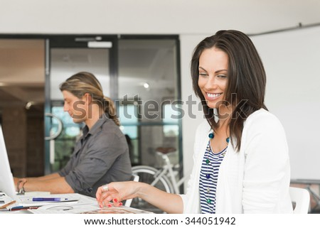 Young coworkers sitting at desk and working on computer