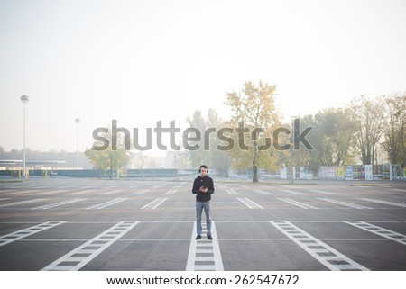 young crazy funny asian man in town outdoor lifestyle listening music with headphones - intentional backlit - stock photo