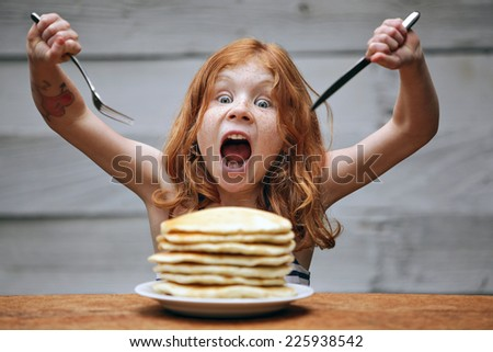 Young crazy girl eating a stack of pancakes.
