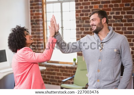 Young creative business people high fiving at the office - stock photo