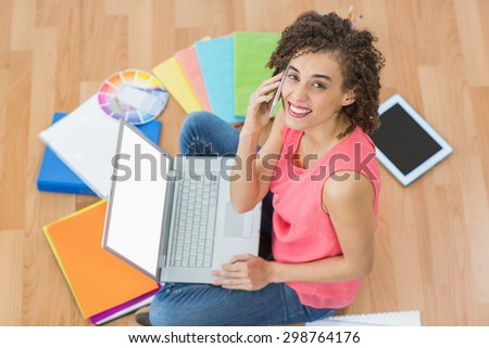 Young creative businesswoman working on laptop while on the phone - stock photo