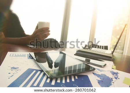 Young creative designer man working at office and holding a cup of coffee and social network media diagram as concept - stock photo