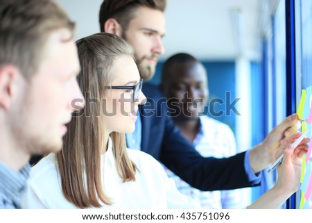 young creative startup business people on meeting at modern office making plans and projects with post stickers on glass - stock photo