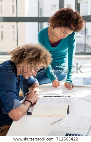 Young Creative Student Writing Observations And Ideas For An Assignment While Sitting At Desk Next To