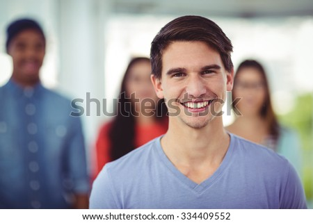 Young creative team smiling at camera in casual office - stock photo