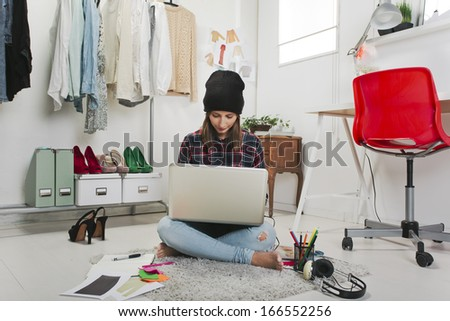 Young creative woman sitting in the floor with laptop./  Casual blogger woman working in her fashion office.
