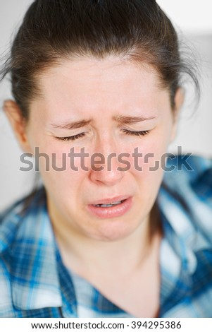 Young crying painful woman, portrait with very shallow deep of field - stock photo