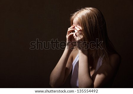 Young crying woman on a dark background - stock photo