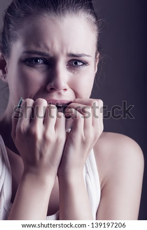 Young crying woman on dark background - stock photo