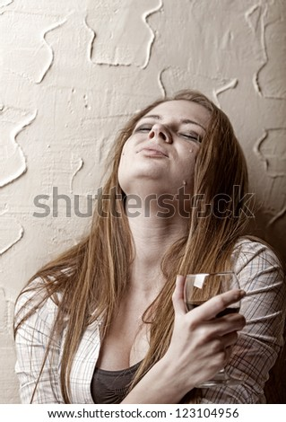 Young crying woman with a glass of wine - stock photo