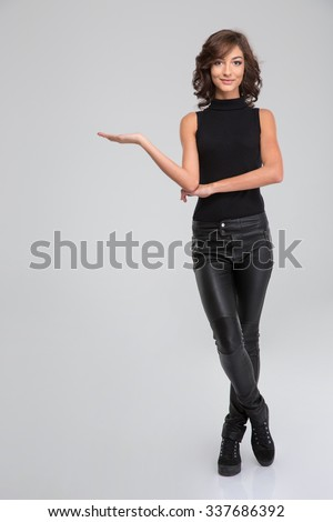 Young curly beautiful attractive female in black leather pants and top holding copyspace on the palm over white background - stock photo