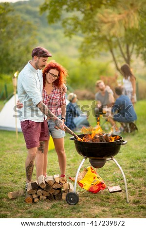 Young curly ginger girl hug boyfriend while he prepare grill fire in camp