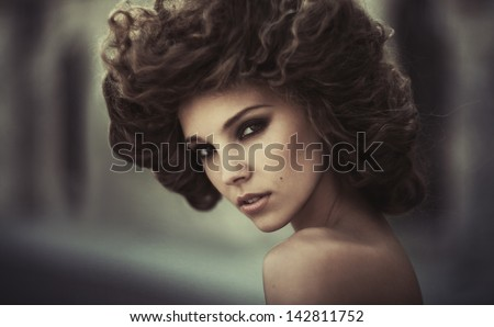 Young curly-haired brunette in an ancient mystical surroundings. Grain added. Color as a creative solution to author - stock photo