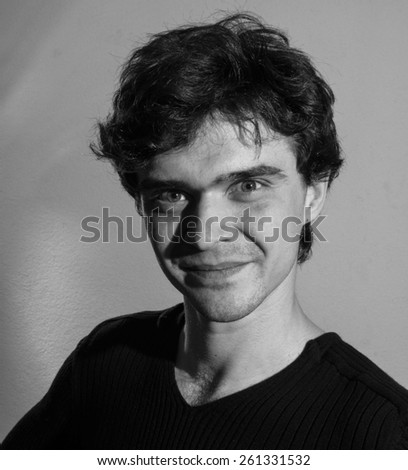 Young curly man in dark jamper - stock photo