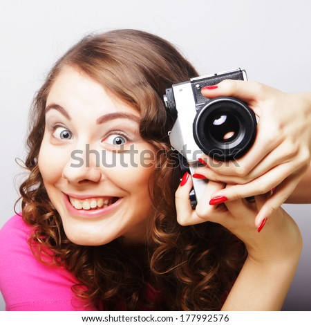 young curly woman with vintage camera