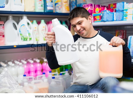 young customer buying detergents for laundry in shopping mall - stock photo