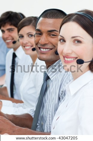 Young customer service agents with headset on in a call center - stock photo