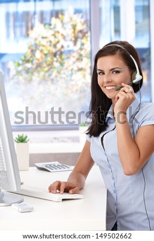 Young customer service operator working in bright office, smiling, looking at camera. - stock photo