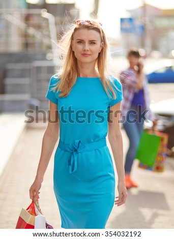 Young customer with shopping bags looking at camera outdoors - stock photo