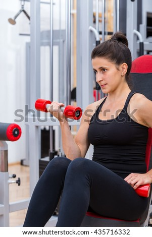 Young, cute, athlete girl in black sportswear, making physical training for the biceps muscle at the gym by performing the seated dumbbell curl. - stock photo
