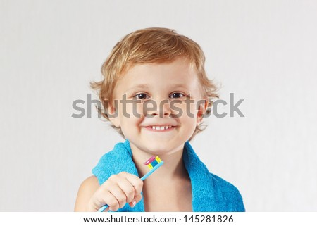Young cute blond boy with toothbrush with pink toothpaste on a white background - stock photo